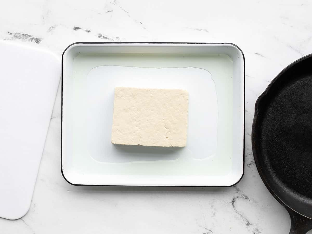 A block of tofu on a baking tray with a cast iron skillet on one side, cutting board on the other side