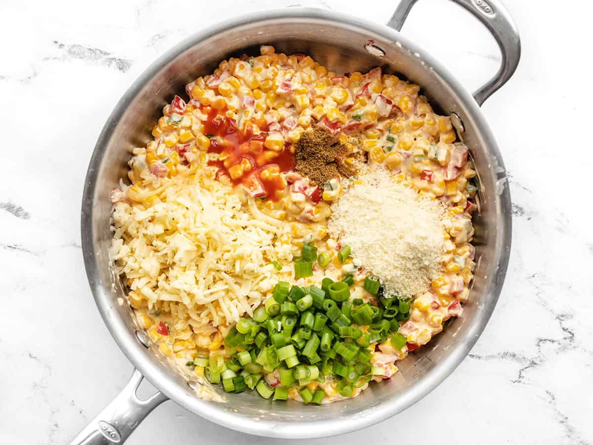 Spices, cheese, and green onion added to the skillet