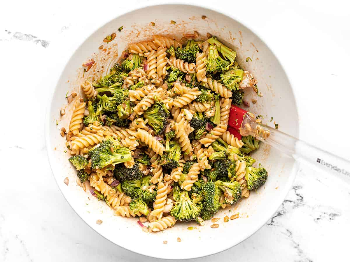 Finished broccoli pasta salad in a bowl with a red spatula