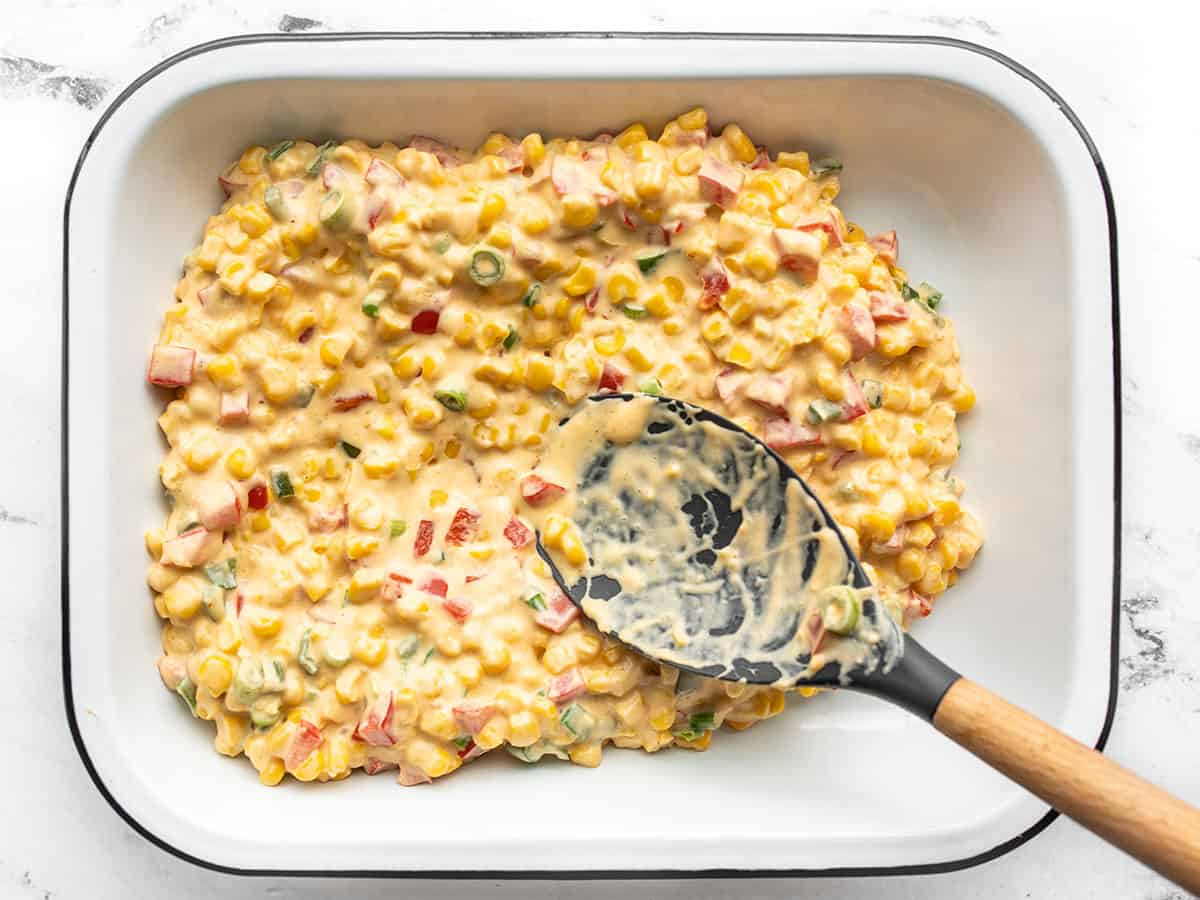 Hot corn dip being spread into a baking dish
