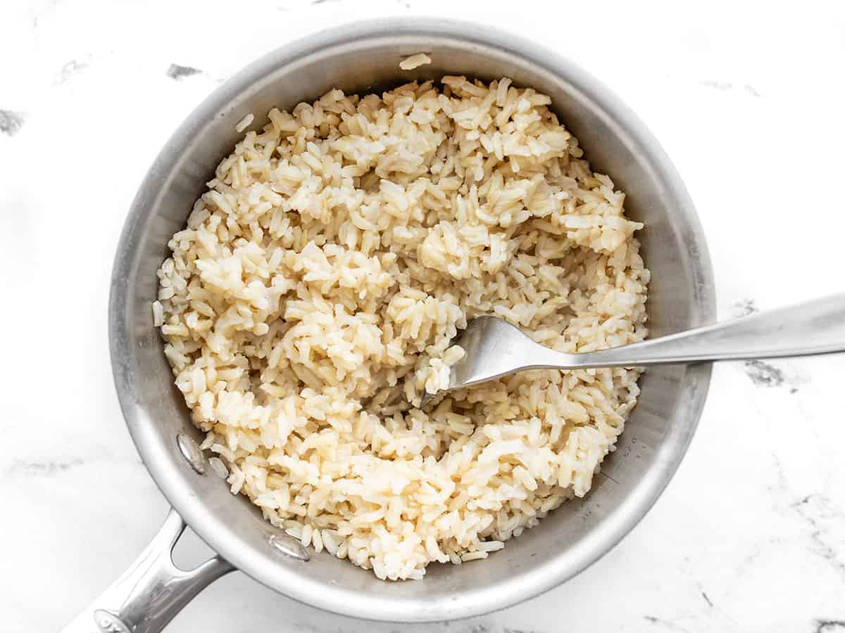 Cooked rice being fluffed with a fork in a saucepot