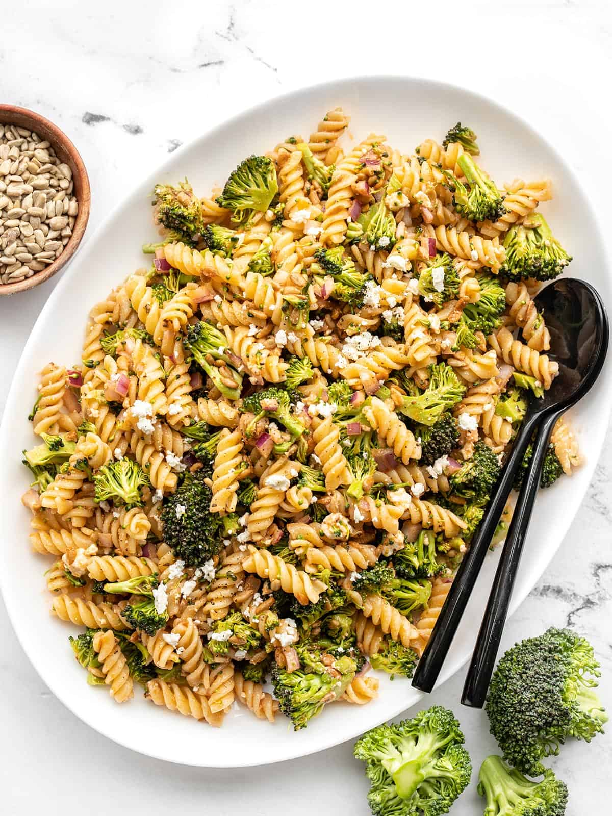 Overhead of an oval serving tray full of broccoli pasta salad with black utensils in the side