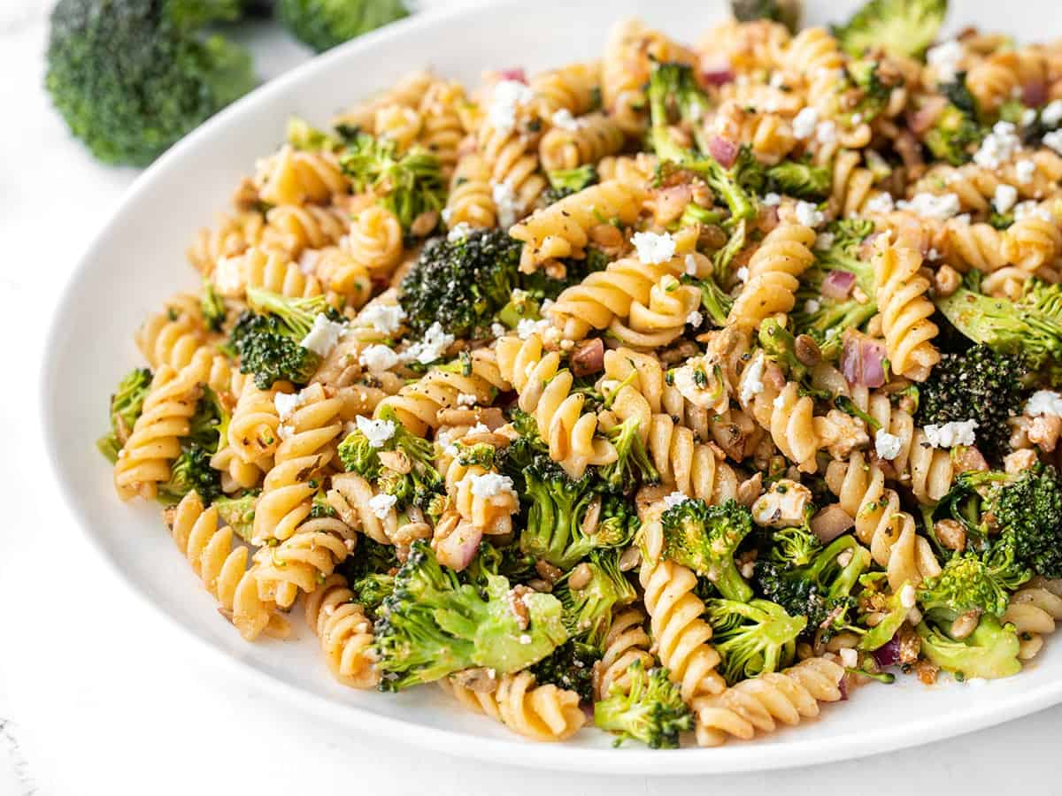 Close up side view of broccoli pasta salad with tomato vinaigrette on a platter
