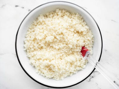 Overhead view of a bowl of riced cauliflower with a red spatula in the side