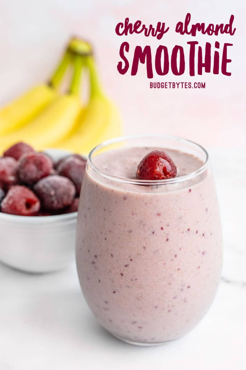 A glass filled with Cherry Almond Smoothie, banana and a bowl of frozen cherries in the back