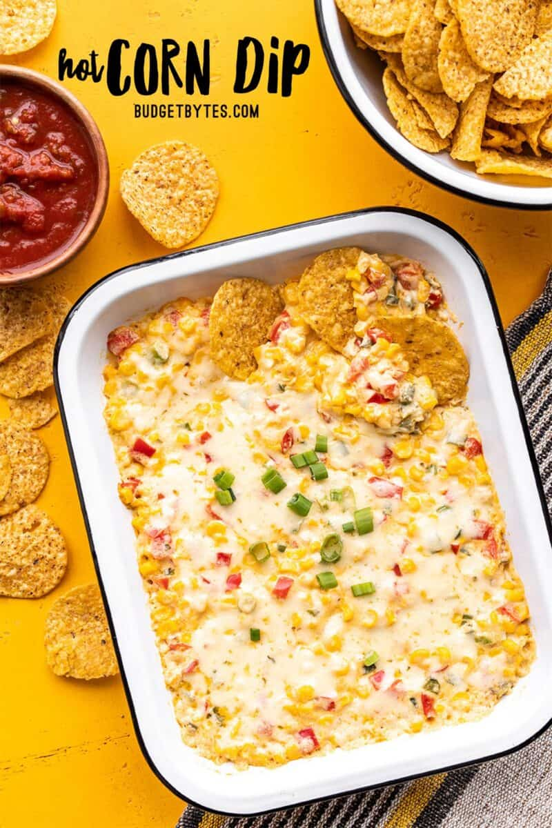 A rectangular casserole dish of hot corn dip with chips and salsa on the side