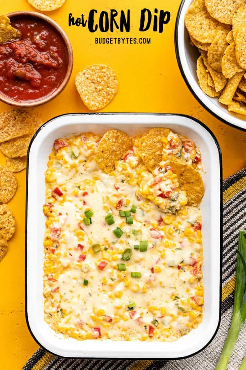 Hot corn dip in a rectangular baking dish, chips and salsa on the sides