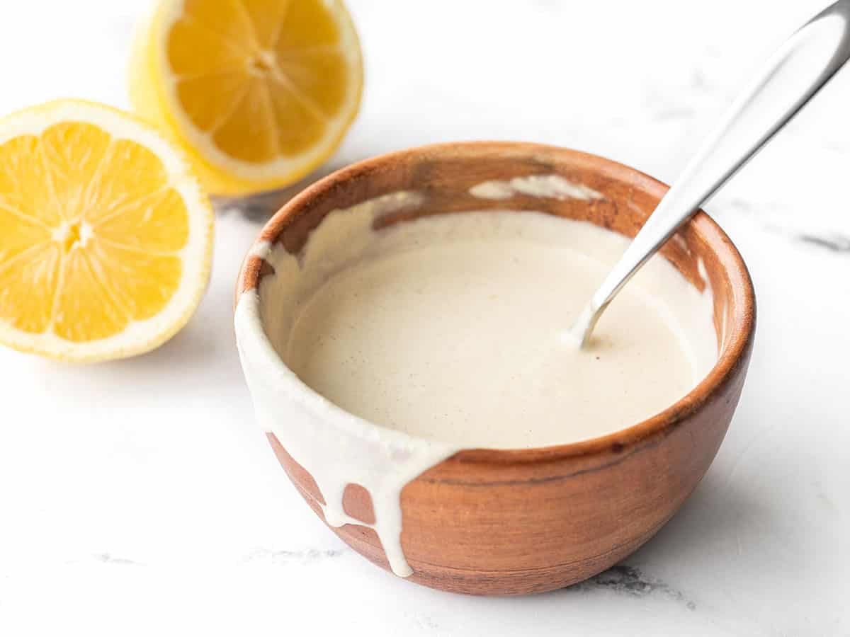 Side view of a wooden bowl with lemon tahini dressing, some dripping down the side