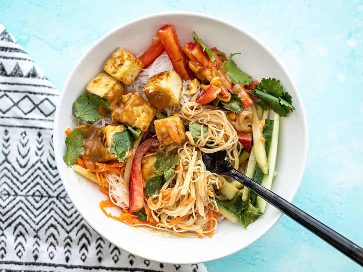 Half-stirred peanut tofu noodle bowl with a fork in the center