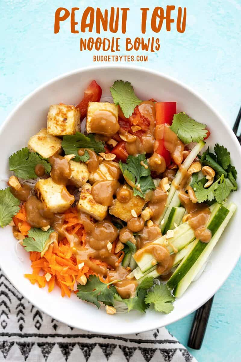 Overhead view of a peanut tofu noodle bowl with title text at the top
