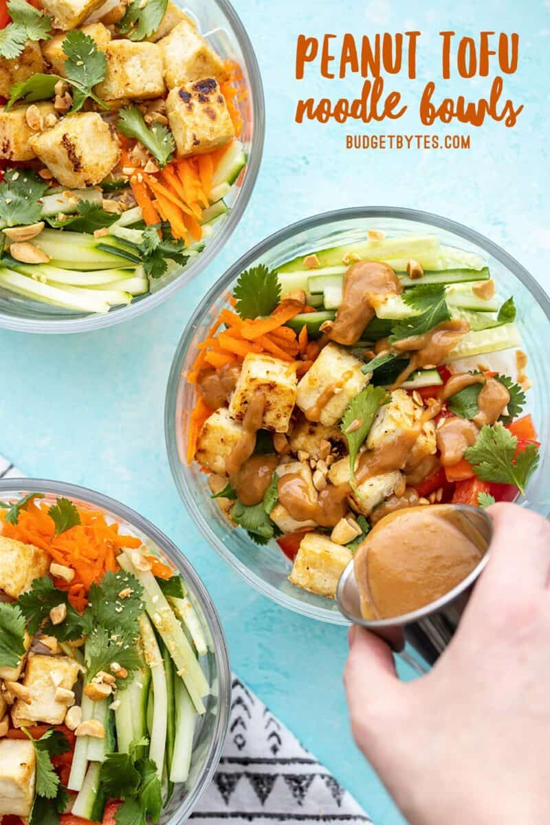 Three peanut tofu noodle bowls with peanut lime dressing being poured over one
