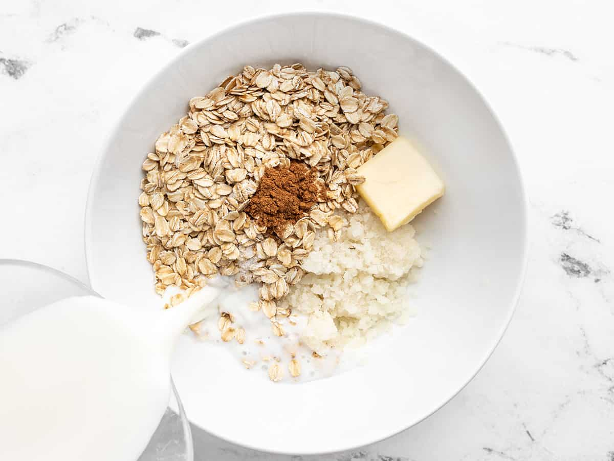 Cauliflower oatmeal ingredients in a bowl, milk being poured in