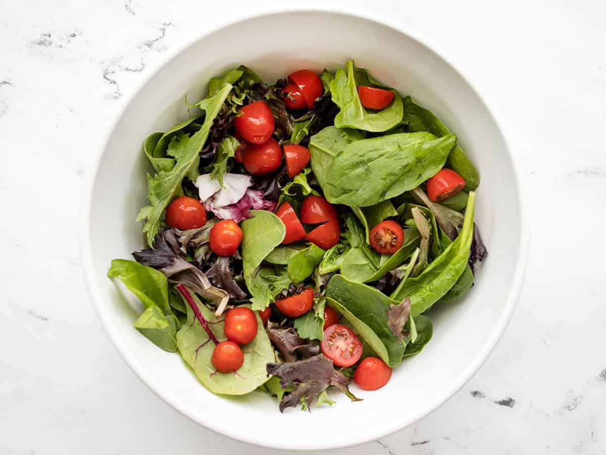 Tomates agregados a las hojas de ensalada