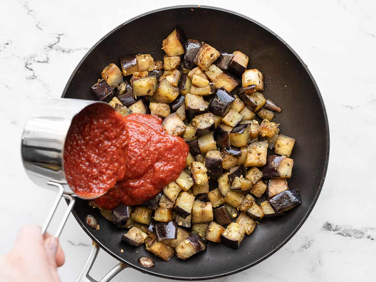 Marinara sauce being added to sautéed eggplant in the skillet