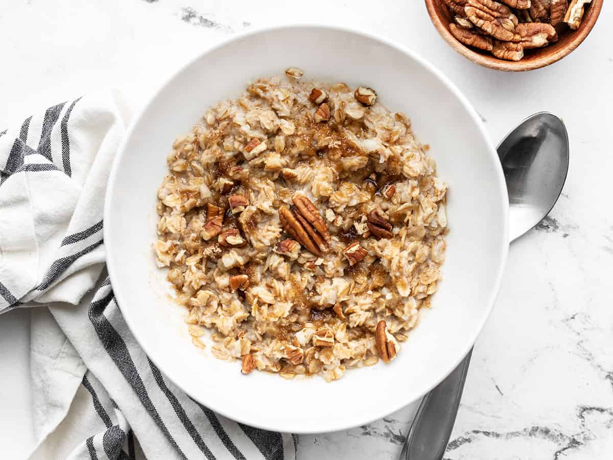 Finished cinnamon pecan cauli oats in a bowl with a spoon on the side