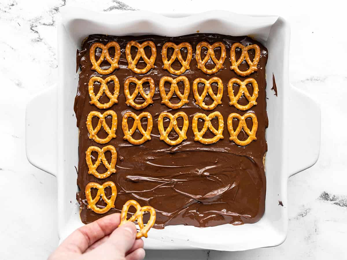 Mini pretzels being pressed into the melted chocolate