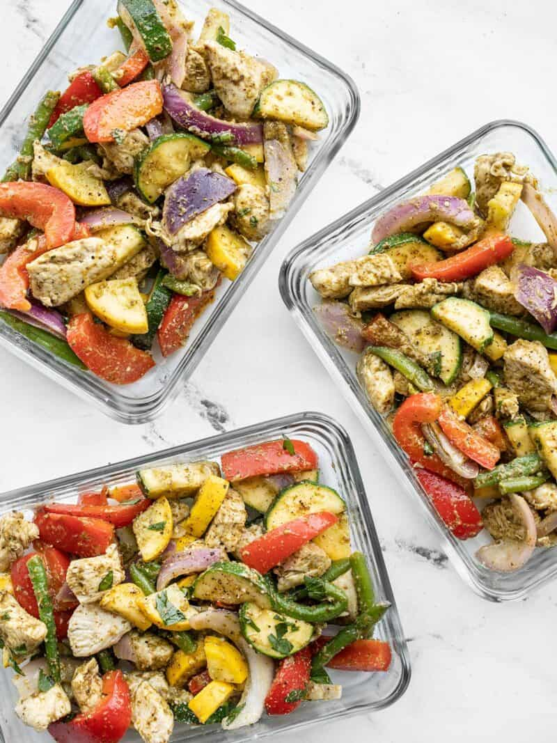 Three glass meal prep containers full of pesto chicken and vegetables