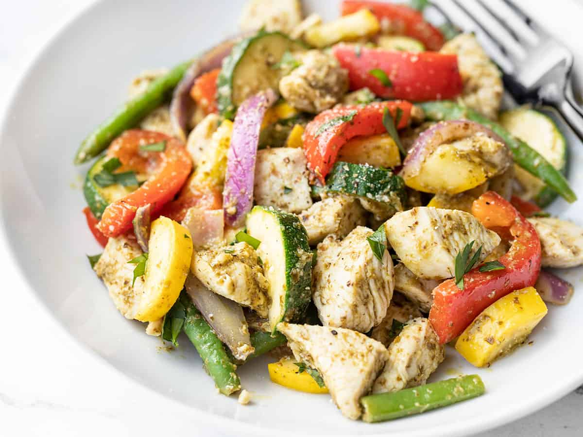 side view of a bowl full of pesto chicken and vegetables