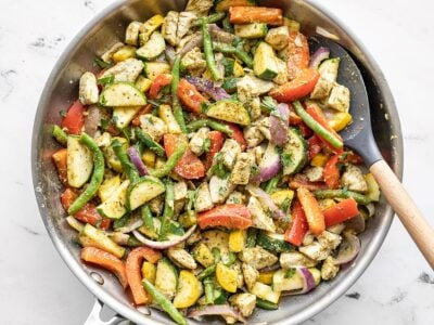 Easy pesto chicken and vegetables in a skillet with a spatula