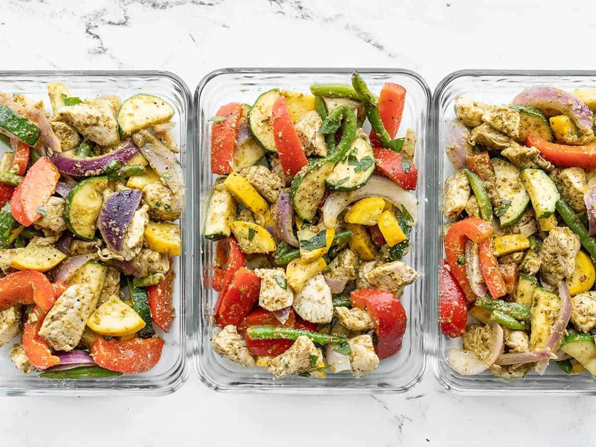 Pesto chicken and vegetables in glass meal prep containers lined up side by side