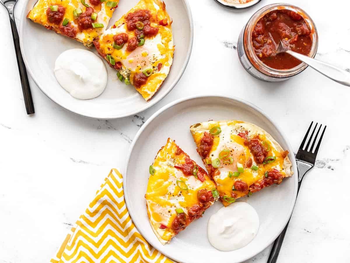 Two servings of tortilla baked eggs with a jar of salsa on the side