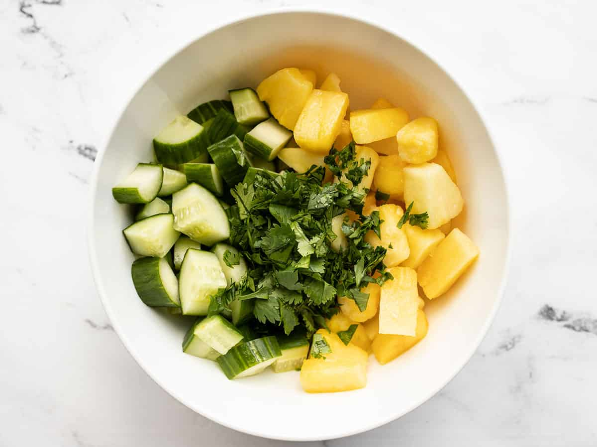 Cucumber, pineapple and cilantro in a bowl