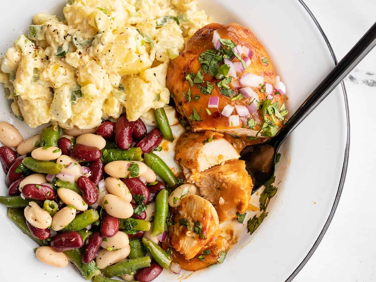 BBQ Cheddar Baked Chicken on a plate with potato salad and bean salad, a fork grabbing a slice of chicken