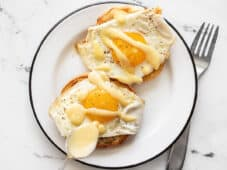 hollandaise sauce being drizzled over two eggs on English Muffins