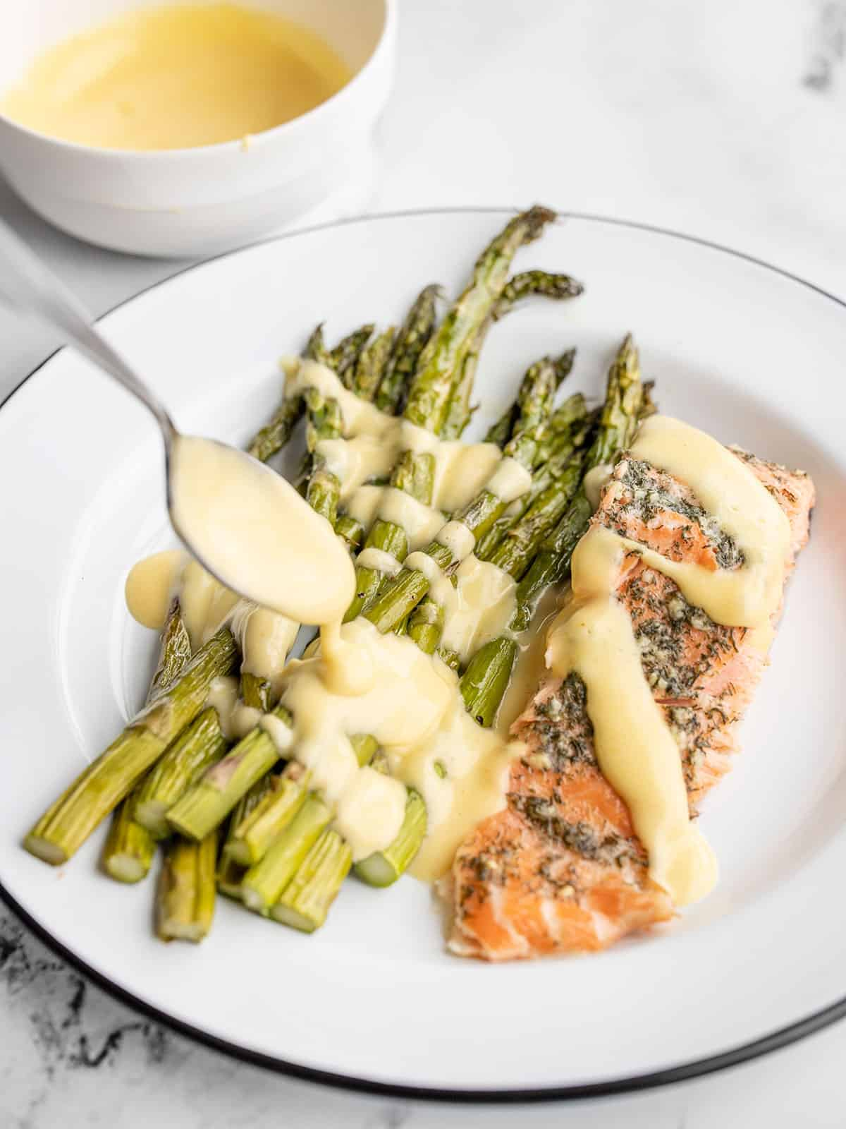 Hollandaise sauce being drizzled over asparagus and salmon