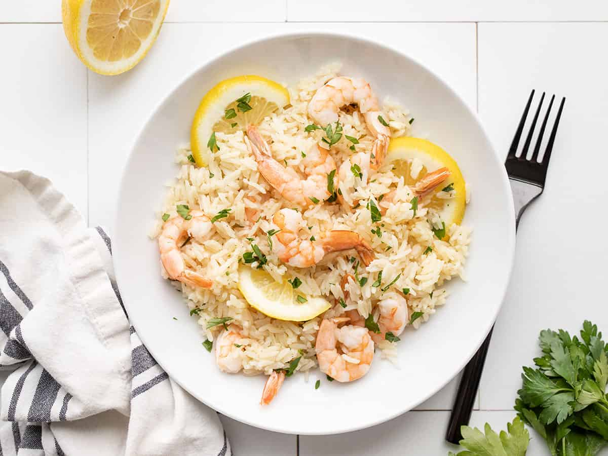 Lemon garlic shrimp and rice on a plate with a fork on the side