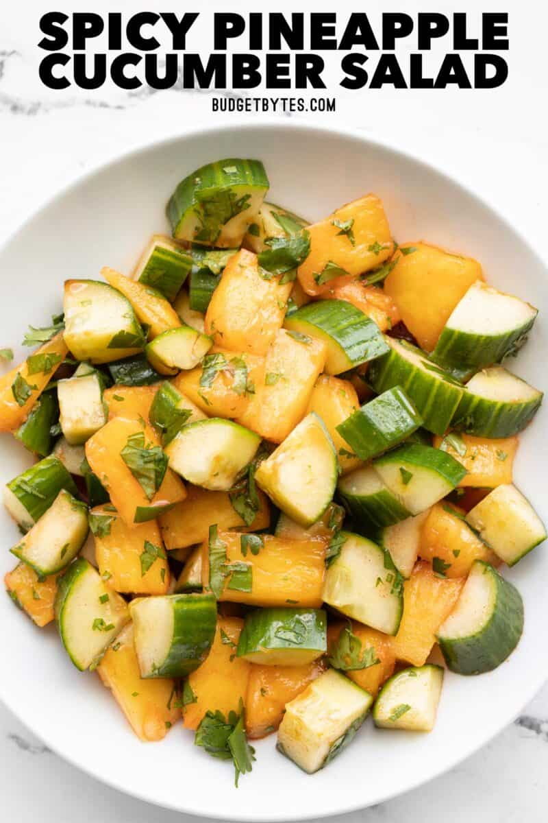overhead view of a bowl full of pineapple cucumber salad, title text at the top
