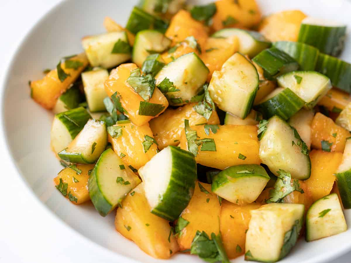 Side view of spicy pineapple cucumber salad in a bowl