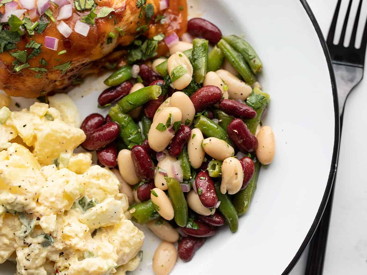 Classic three bean salad on a plate with chicken and potato salad