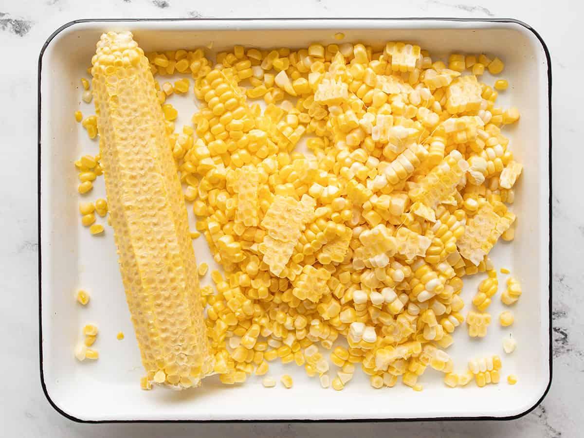 corn kernels sliced off an ear of corn in a baking tray