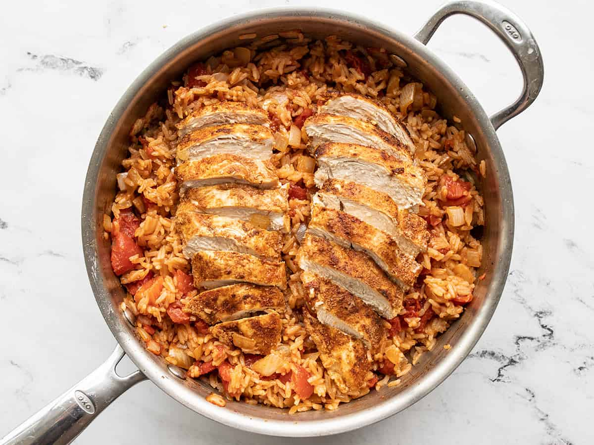 Sliced chicken on top of stirred rice in the skillet