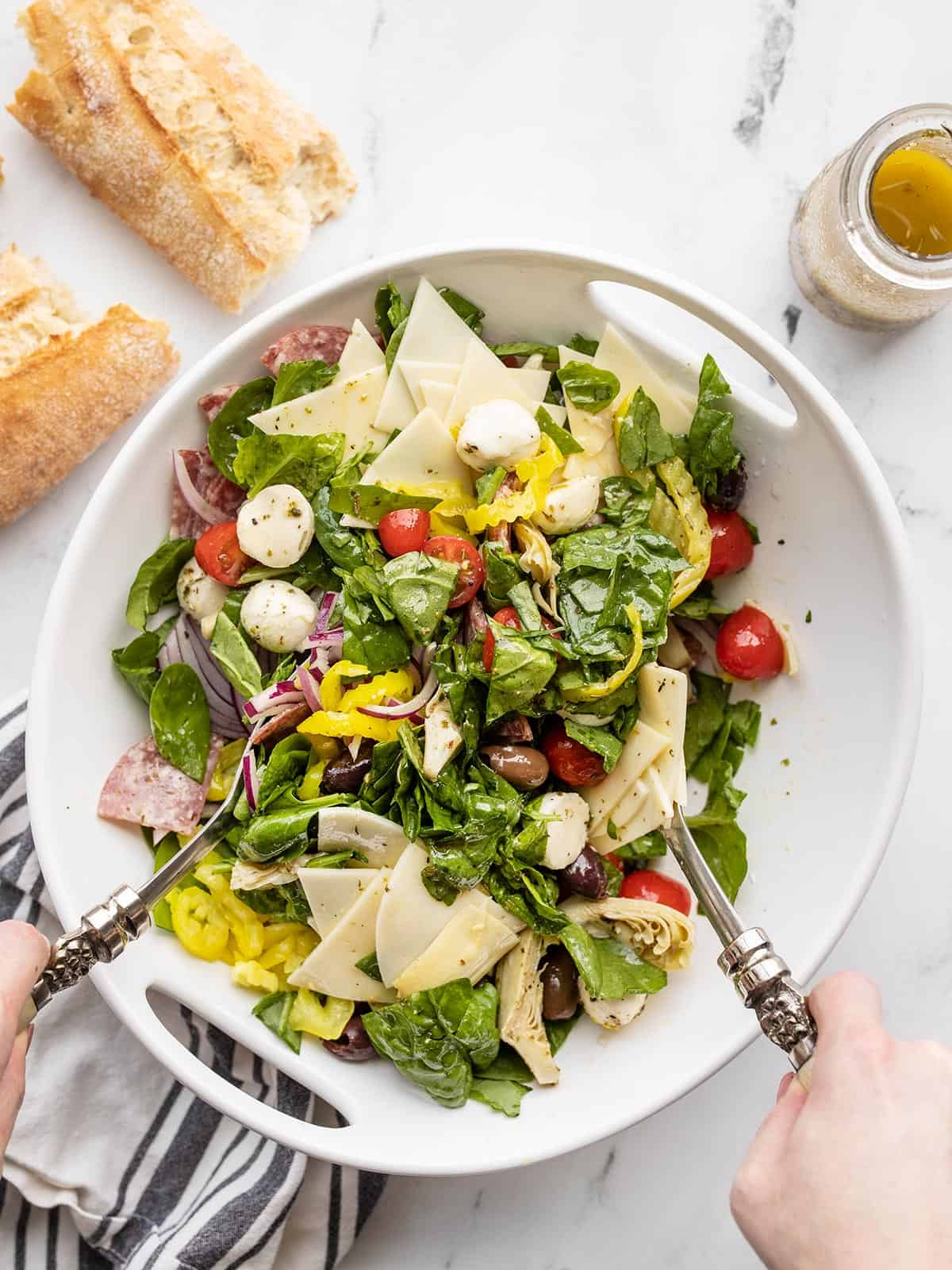 Antipasto salad being tossed with metal salad tongs