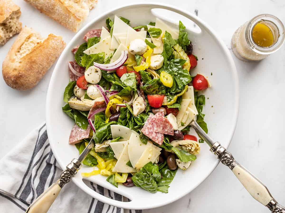 Salad tongs in a half stirred antipasto salad with bread and dressing on the side