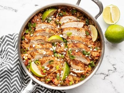 Chipotle lime chicken and rice in the skillet garnished with limes