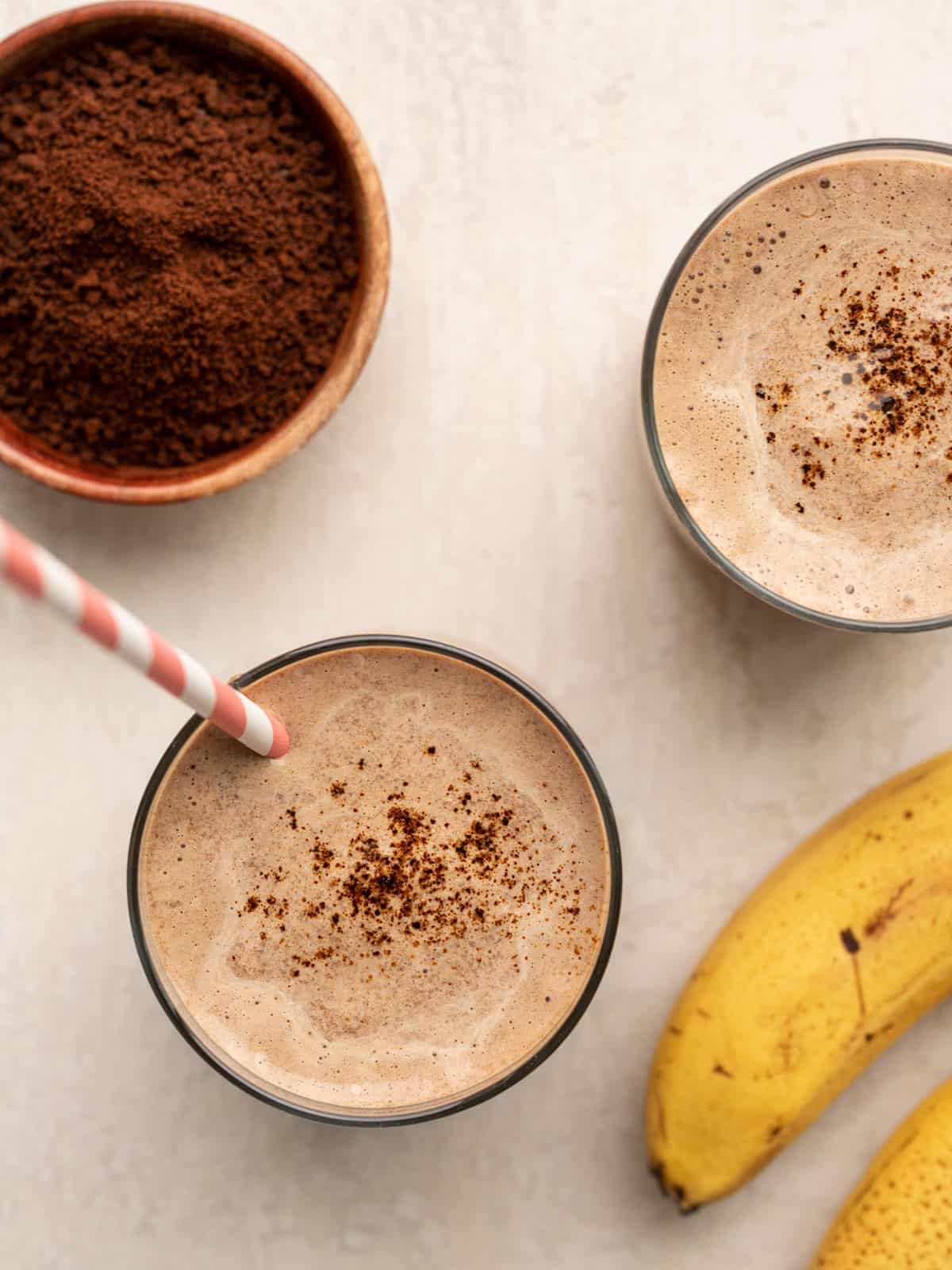 Overhead view of two glasses full of coffee chocolate breakfast smoothies