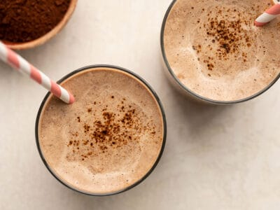 overhead view of two glasses full of chocolate coffee breakfast smoothie with straws