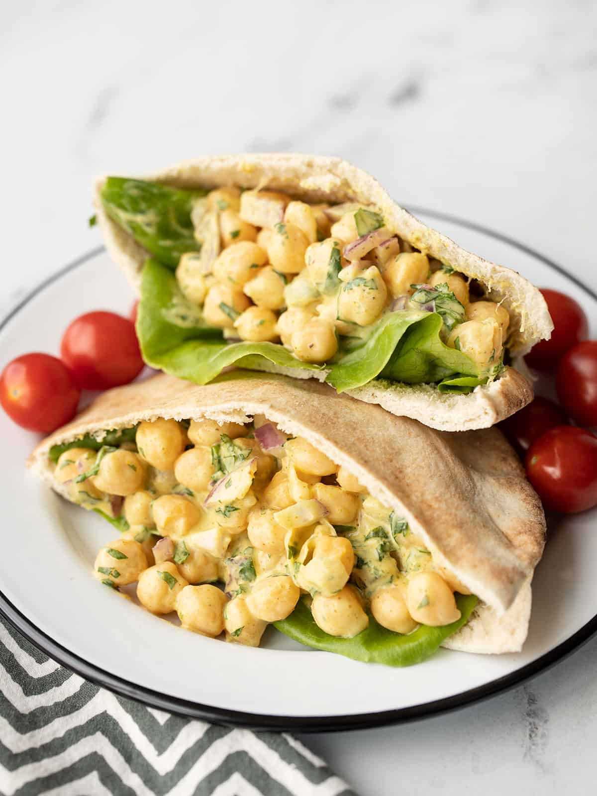 Curry Chickpea Salad stuffed into a pita on a plate with grape tomatoes