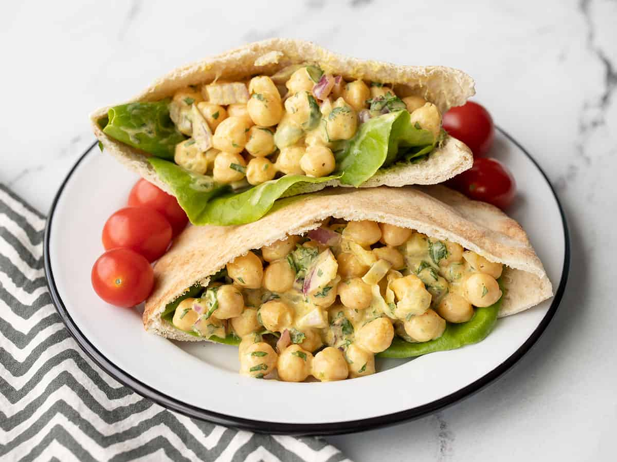 two pita pockets stuffed with curry chickpea salad on a plate with grape tomatoes
