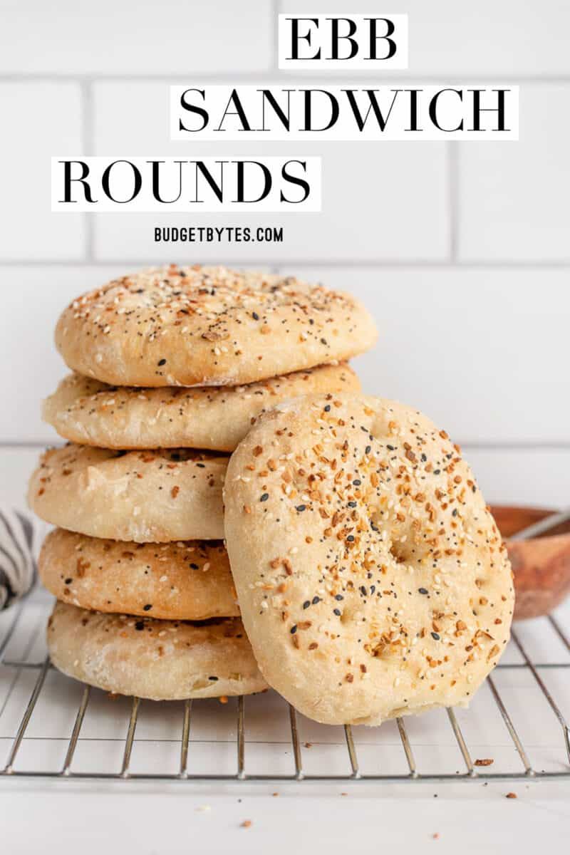 A stack of everything bagel sandwich rounds on a cooling rack, title text at the top