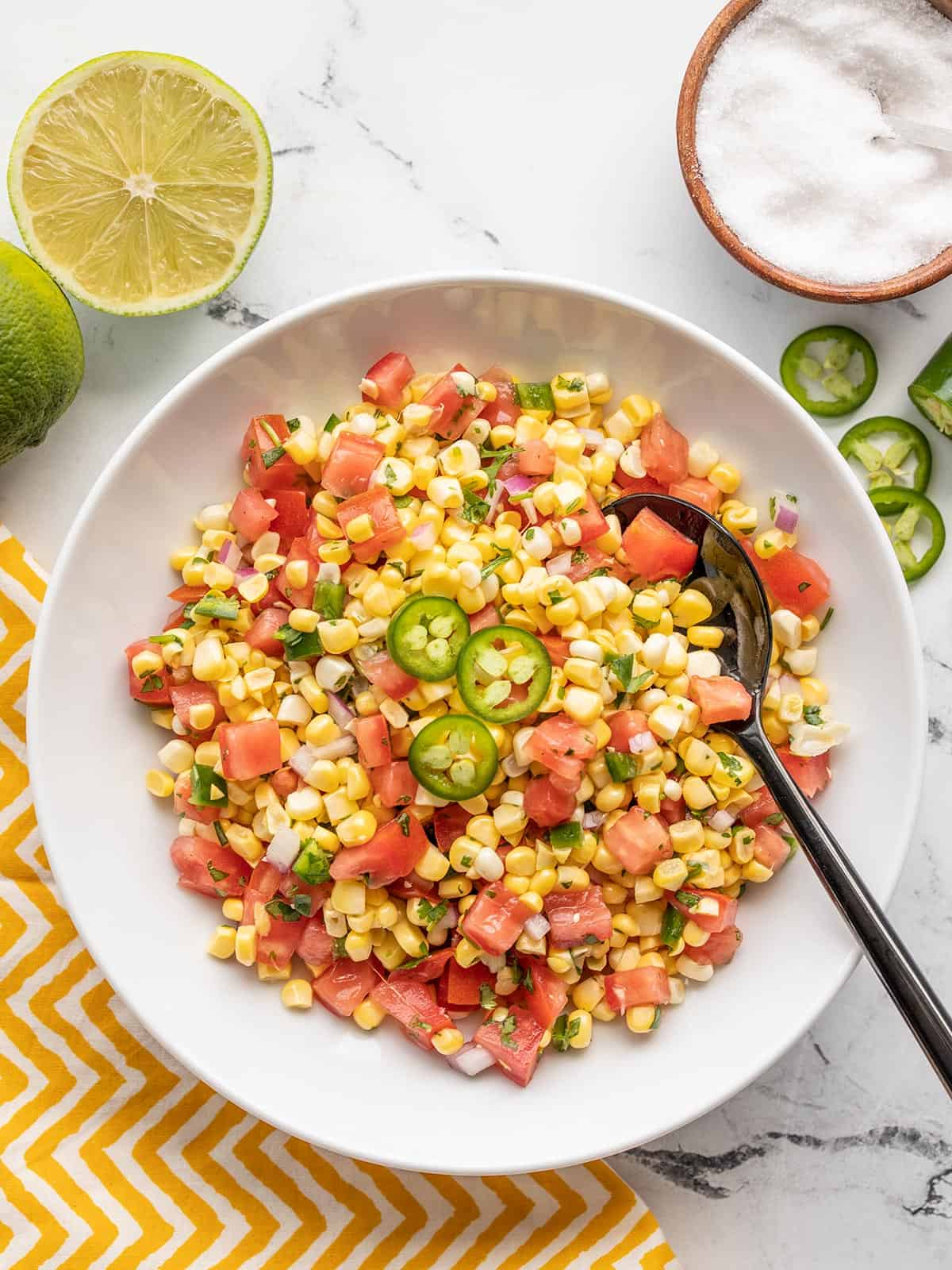 Overhead view of a bowl of sweet corn salsa with lime and salt on the side