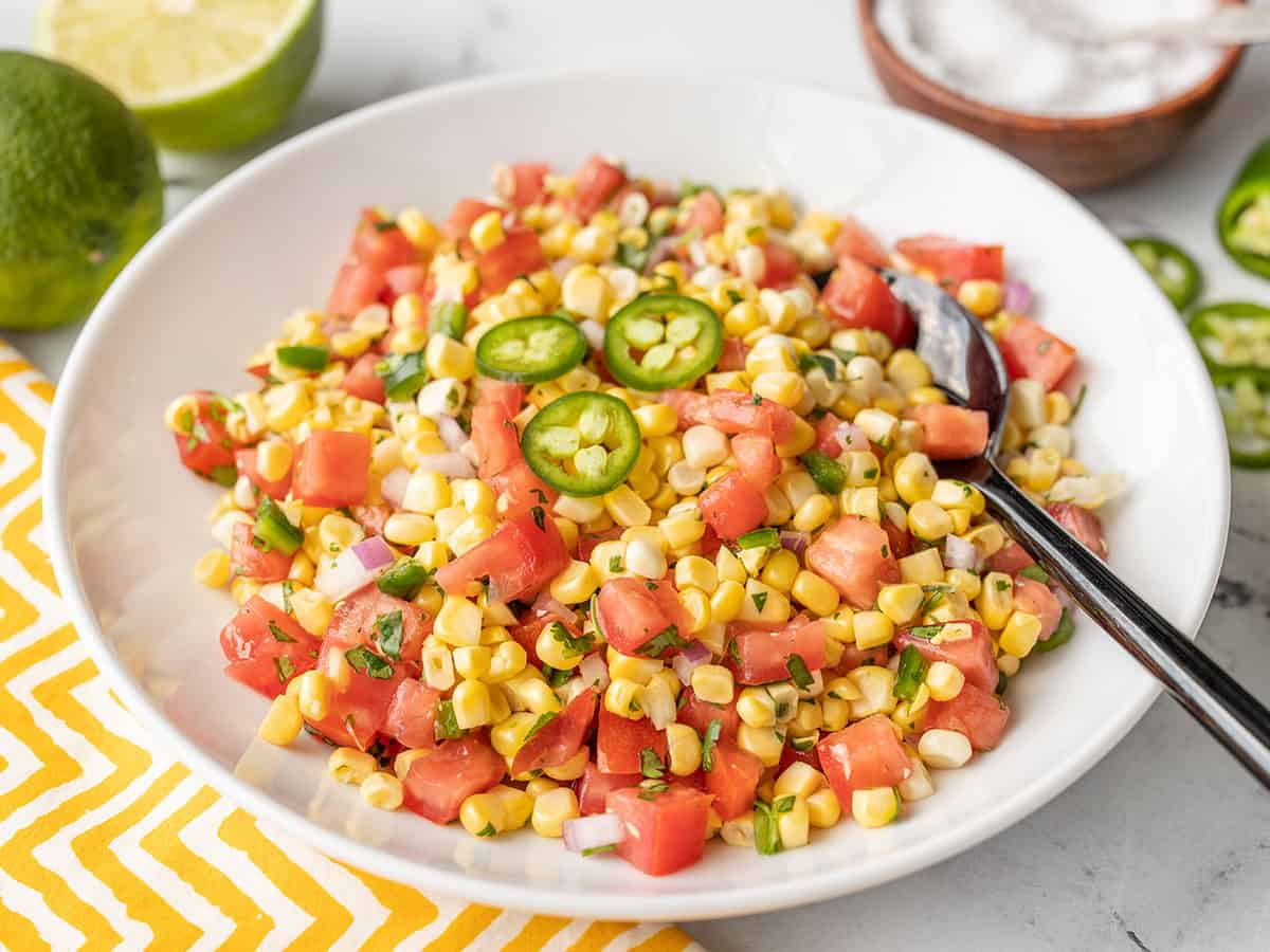 side view of a bowl full of fresh sweet corn salsa