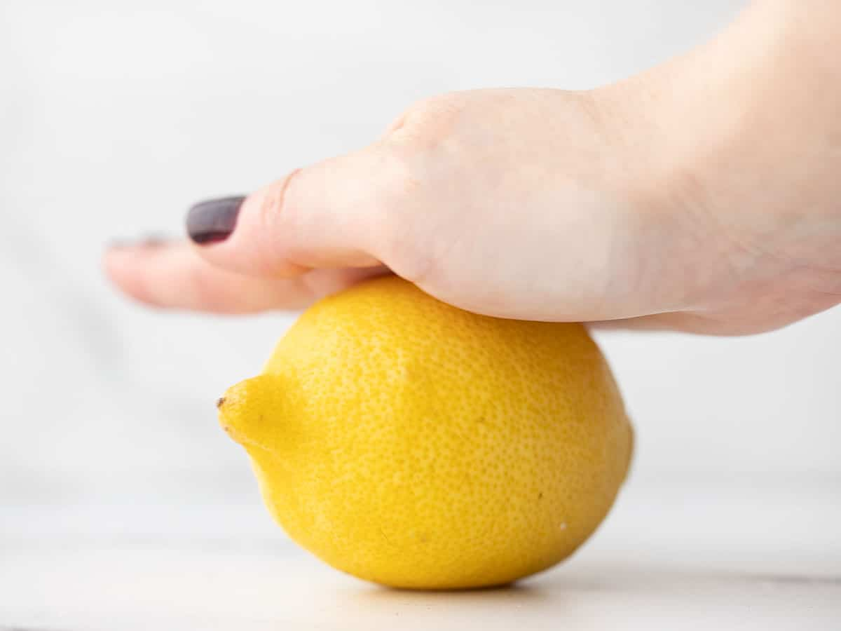 A lemon being rolled on a countertop