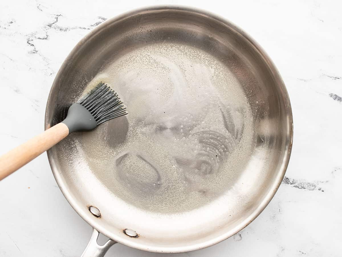 melted butter being brushed over the inside of a skillet