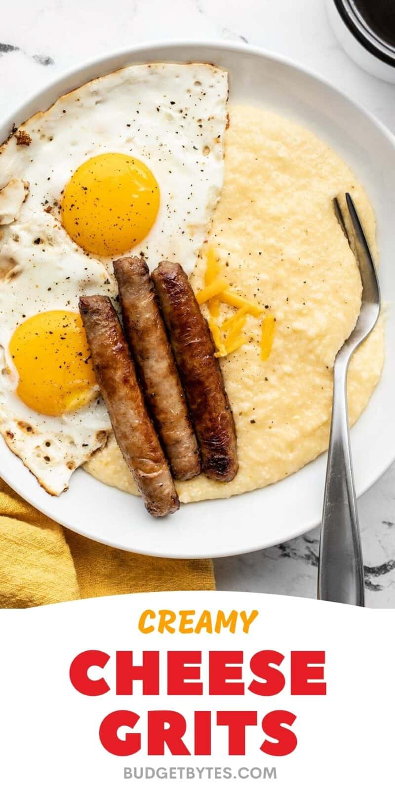 cheese grits on a plate with eggs and sausage, title text at the bottom