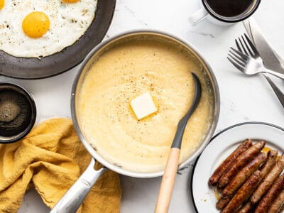 a pot of cheese grits surrounded by other breakfast items