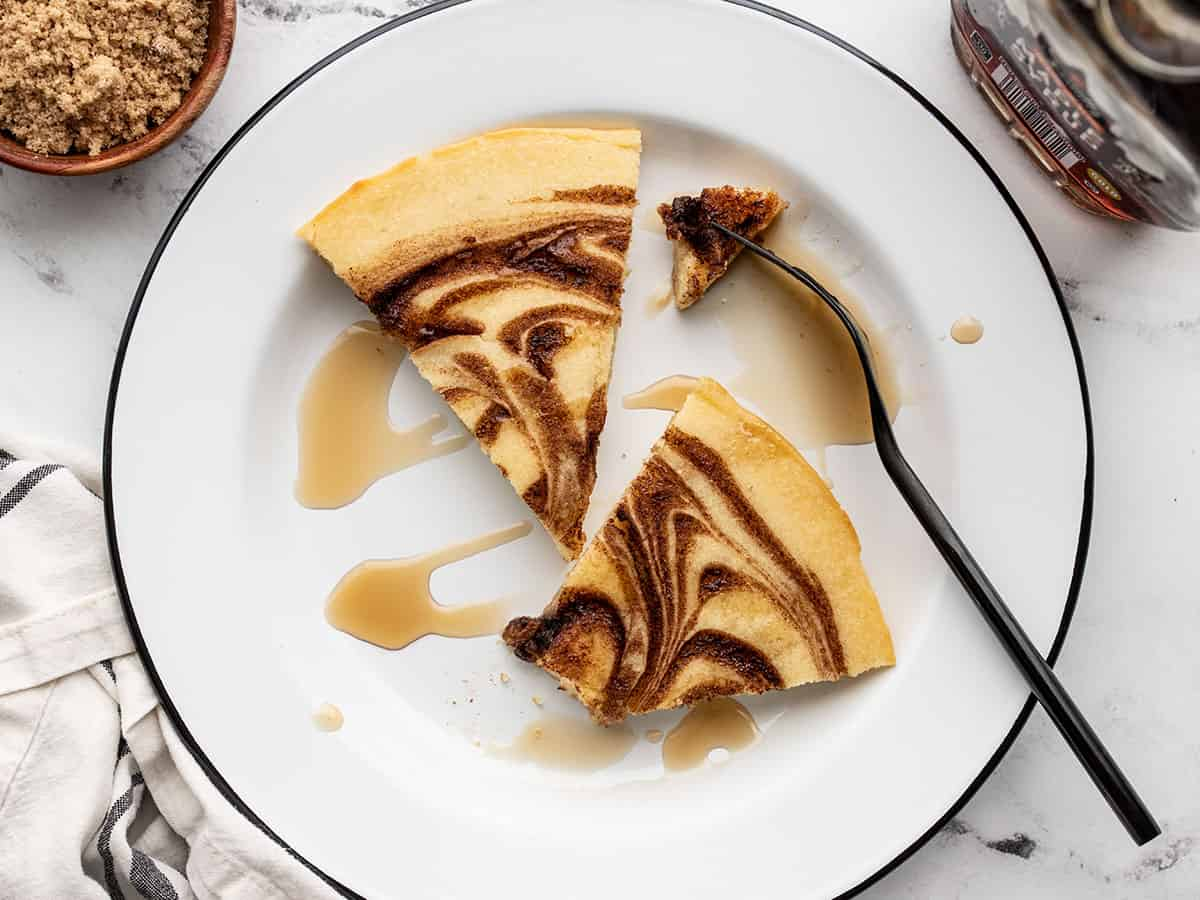 Two slices of cinnamon swirl oven pancake on a plate with a fork and maple syrup